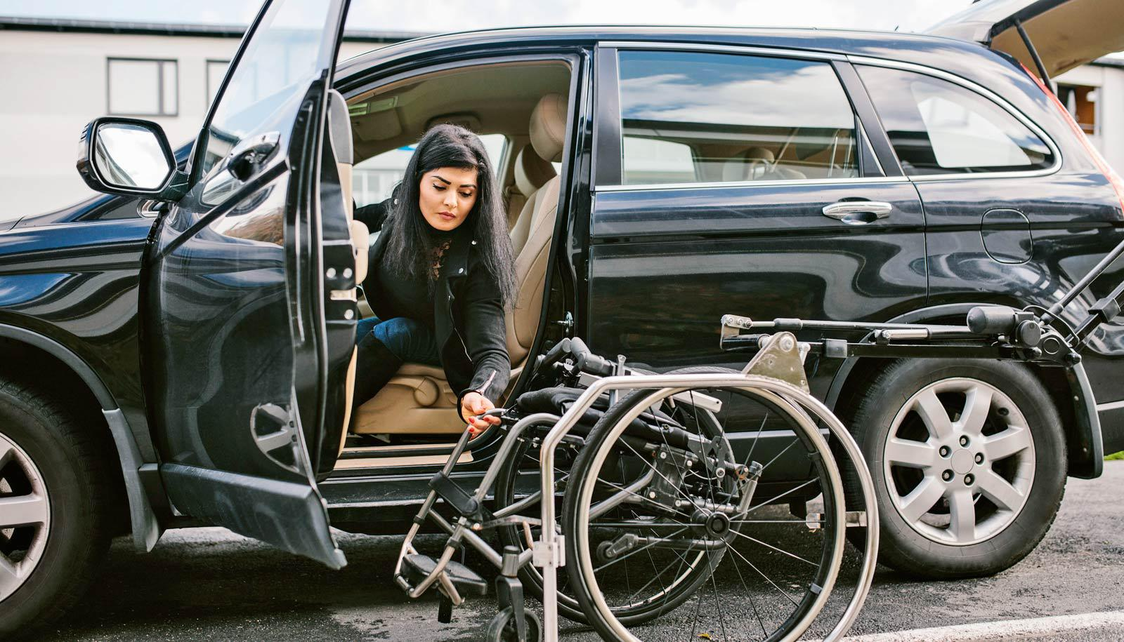 ableism concept - woman with disabilities leans out of car toward wheelchair