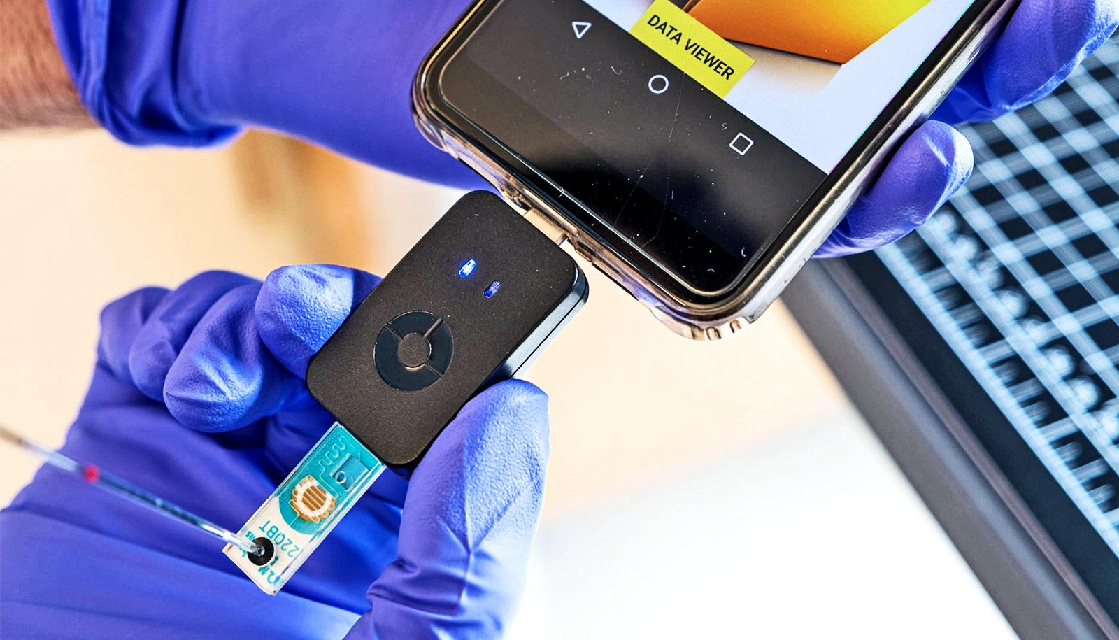 A researcher wearing purple gloves holds the small black device plugged into the phone. The device has a blue chip coming out of the bottom.