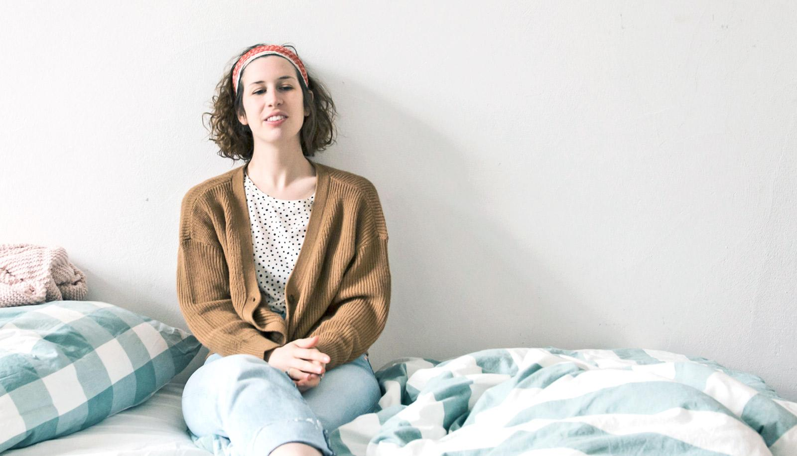 young woman sits on bed - first-year students