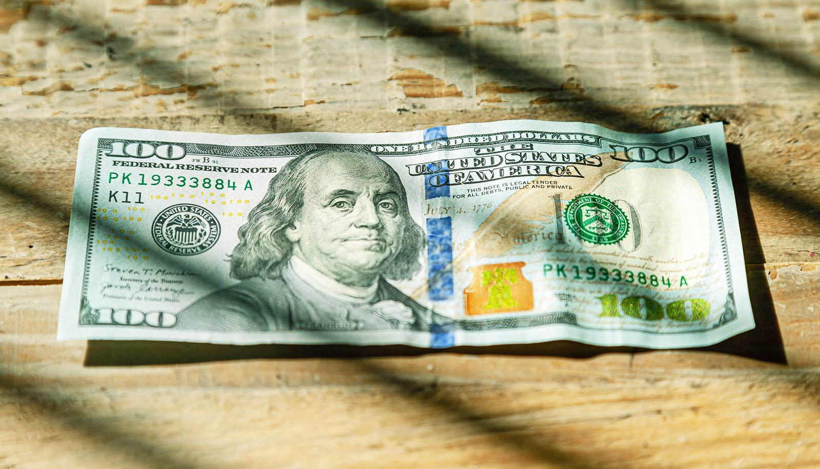 $100 bill on wood surface