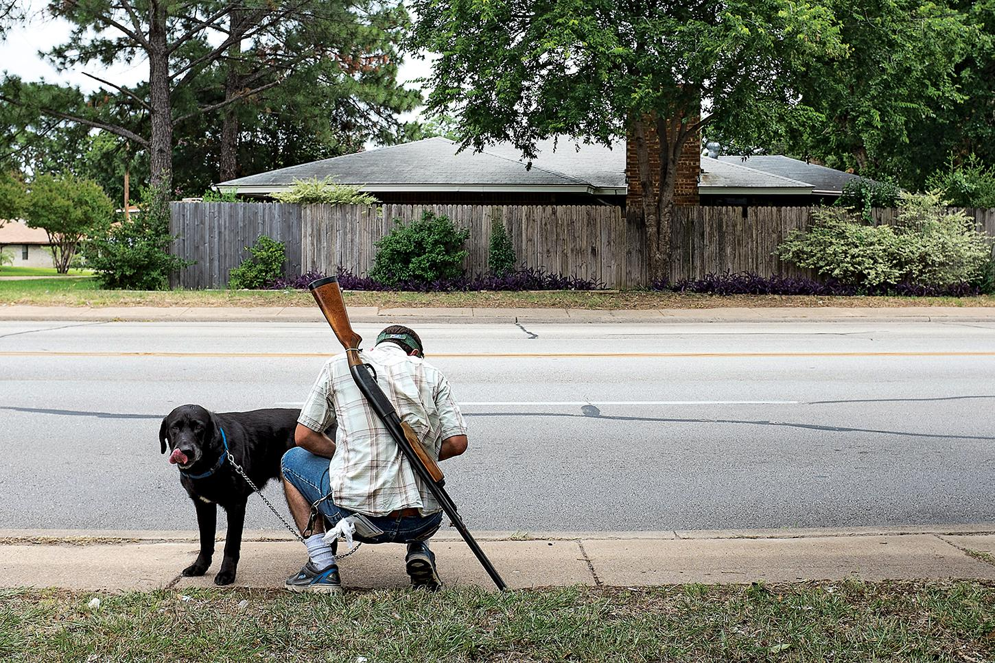 Michael Forster Jr. with his dog and his Remington shotgun during an open carry demonstration in Irving, Texas, on June 21, 2014.