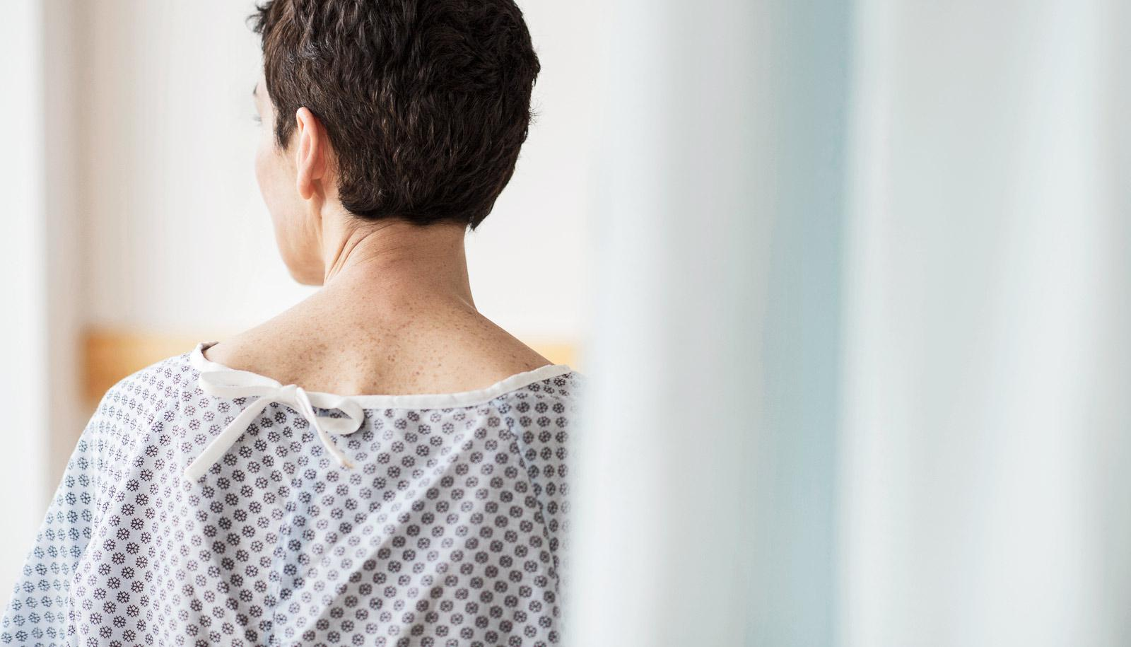 hospital patient in gown facing away