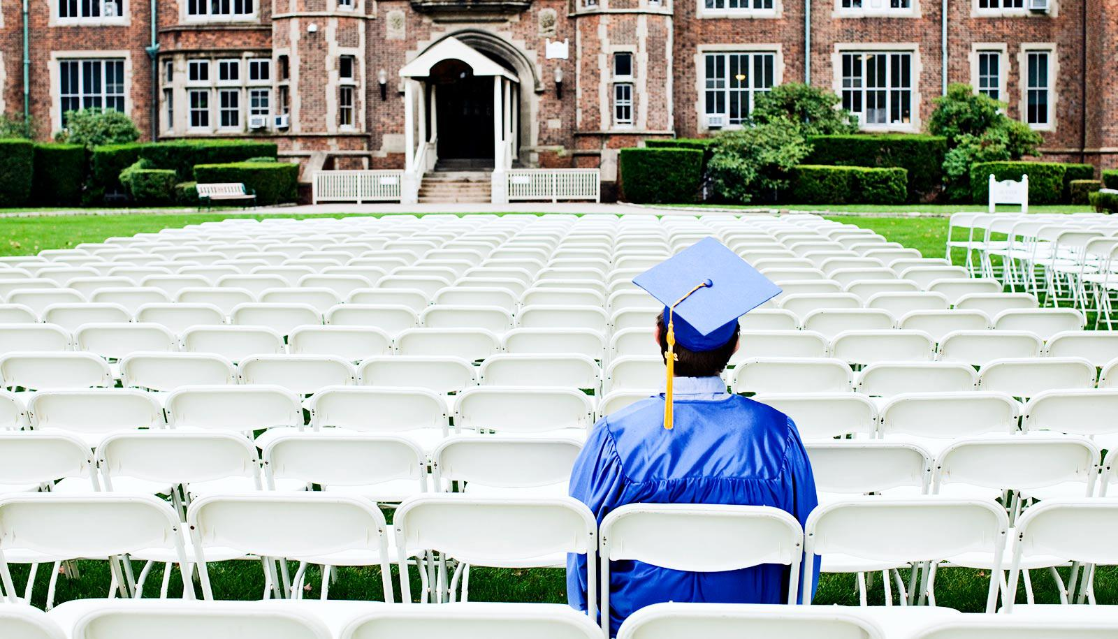 A student sits alone at an empty graduation ceremony in blue cap and gown