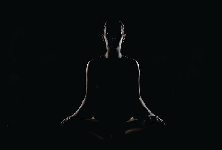 Finding Solace in Silence by Judy Marano. Photograph of a silhouette of a person meditating in the dark by Max Rovensky