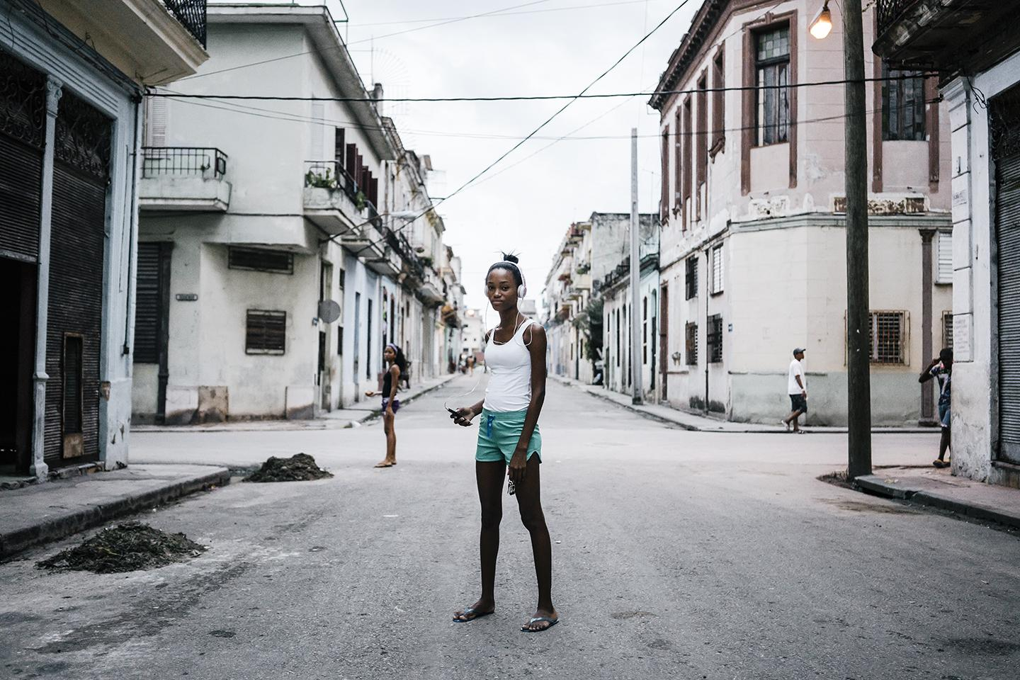 Anna Marie Mesa, 16, listens to music on her smartphone in Centro Havana. Technology is leapfrogging the infastructure in Cuba where citizens went from landlines to smartphones in a matter of months.