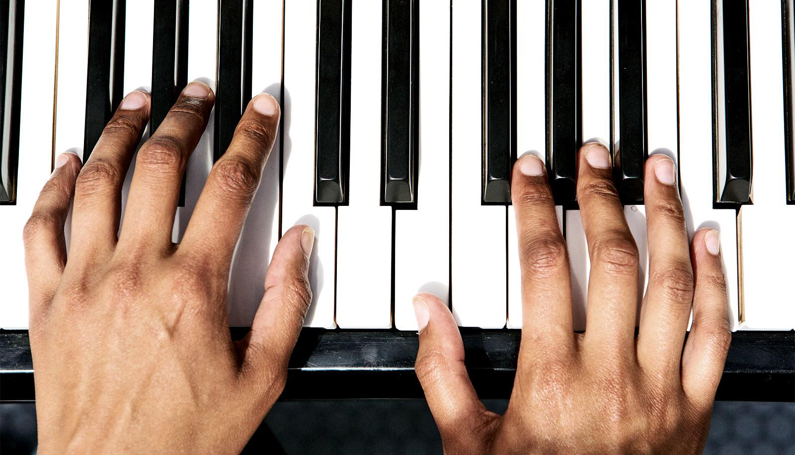Two hands sit on piano keys