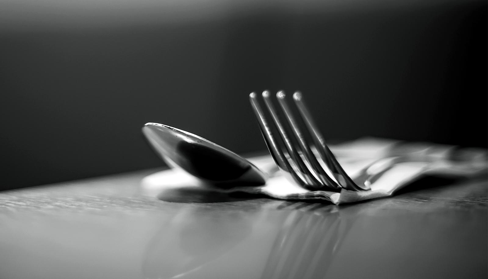 A black and white shot of a fork and spoon on a table
