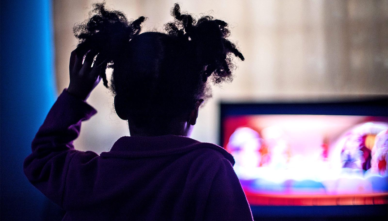 A young girl watches TV