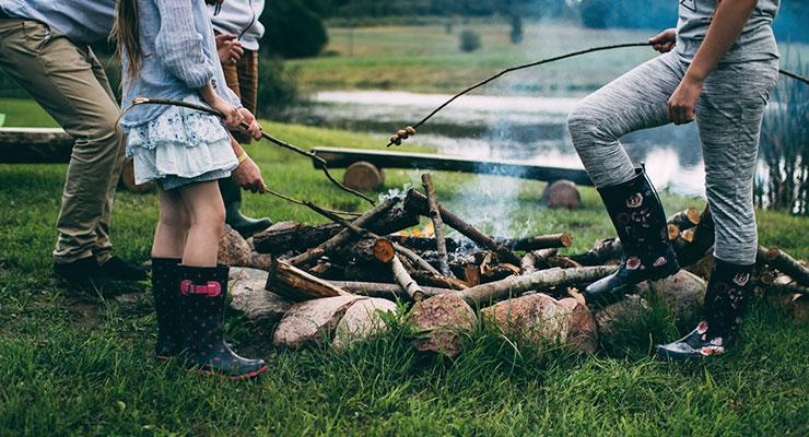 Family Time: 6 Tips for Creating & Maintaining Strong Family Bonds by Nora Mork. Photograph of family cooking stores over a campfire by Daiga Ellaby