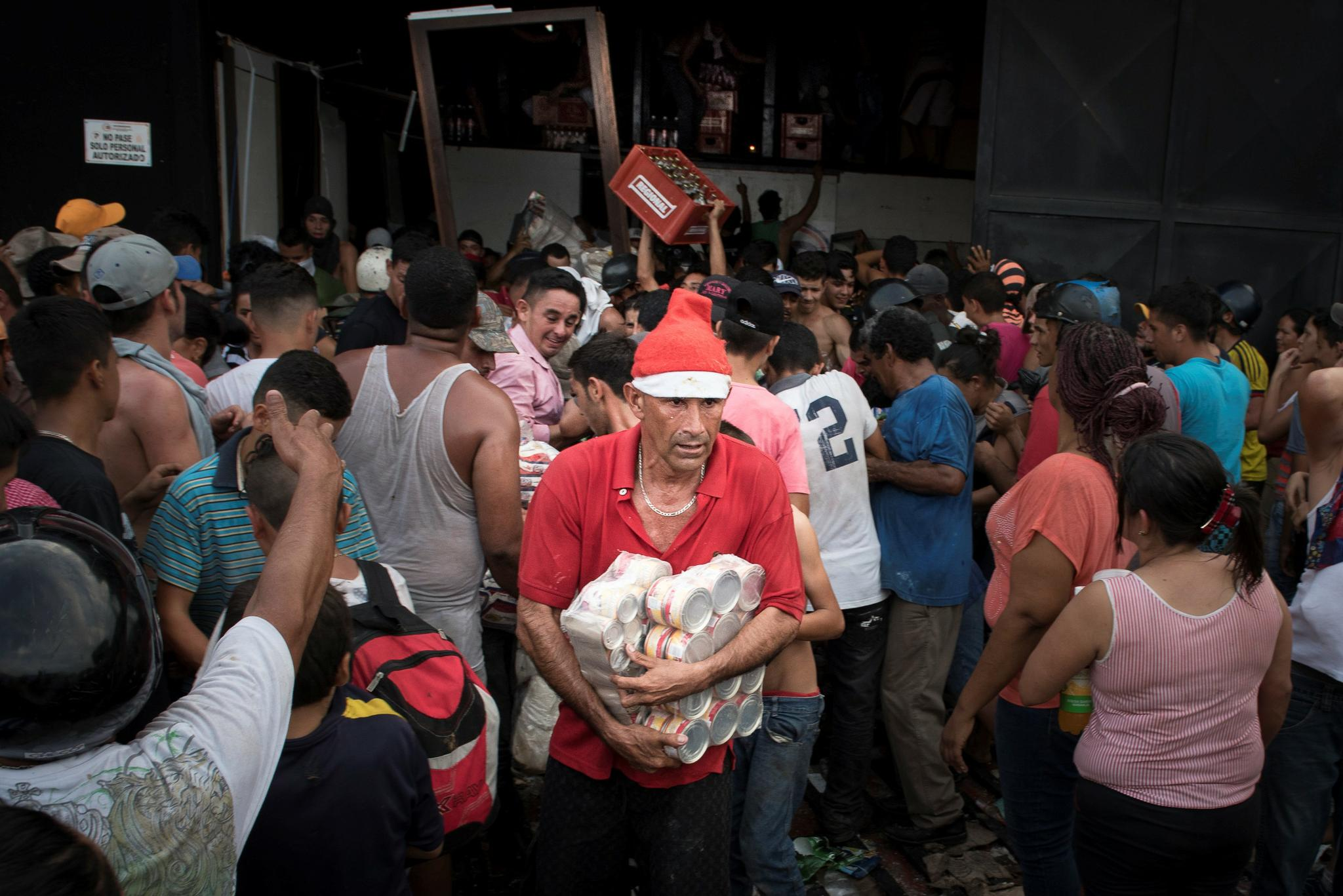 People carry cans of food and bottles of drinks as they loot a food warehouse during a protest in La Fria, Tachira, Venezuela, on December 17, 2016. As Venezuela's economic crisis worsens, the grocery stores are empty, and a local prison doubles as makeshift supermarket.