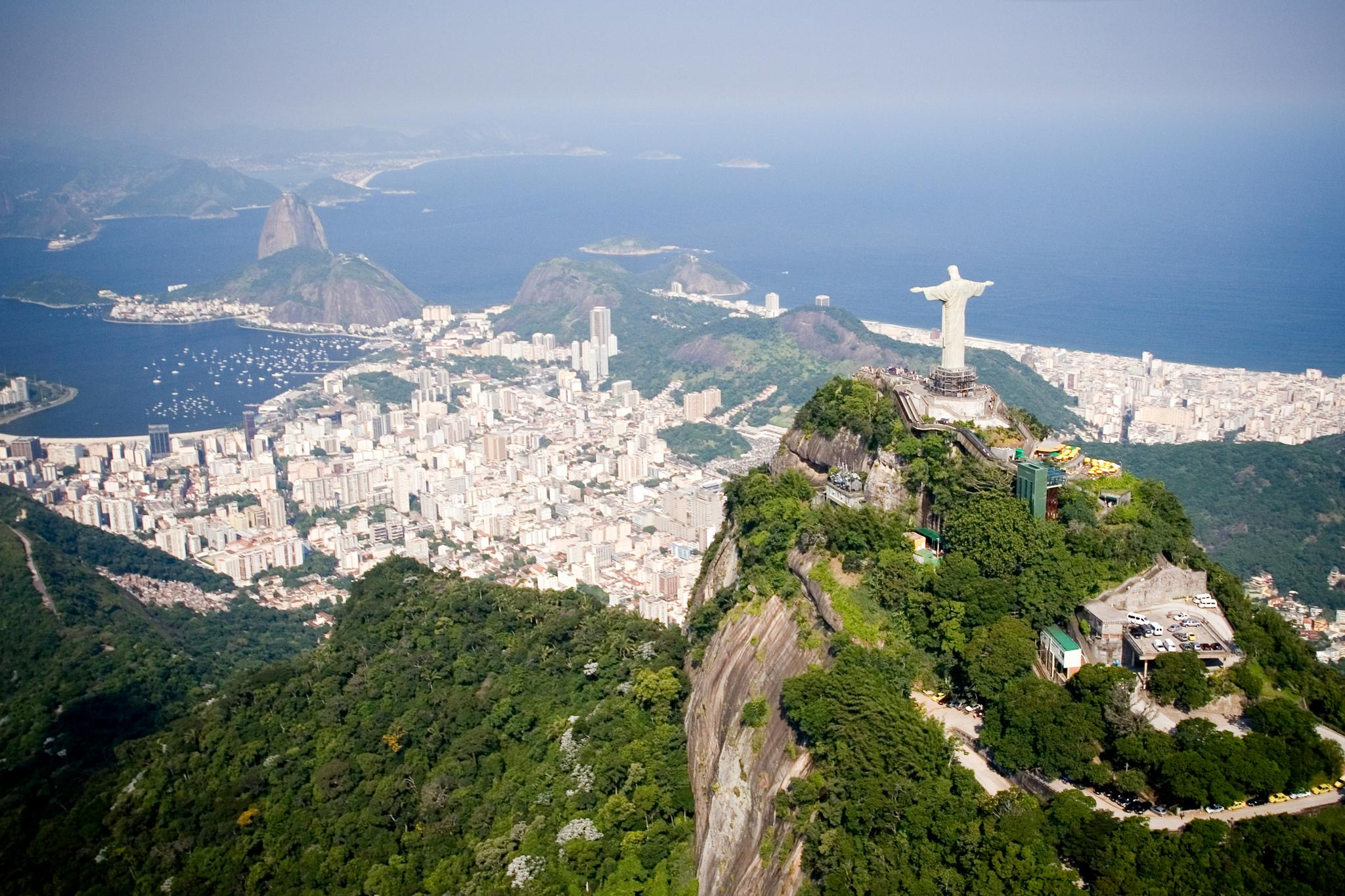 An aerial view of Rio de Janeiro features landmarks Christ the Redeemer and Sugarloaf Mountain.