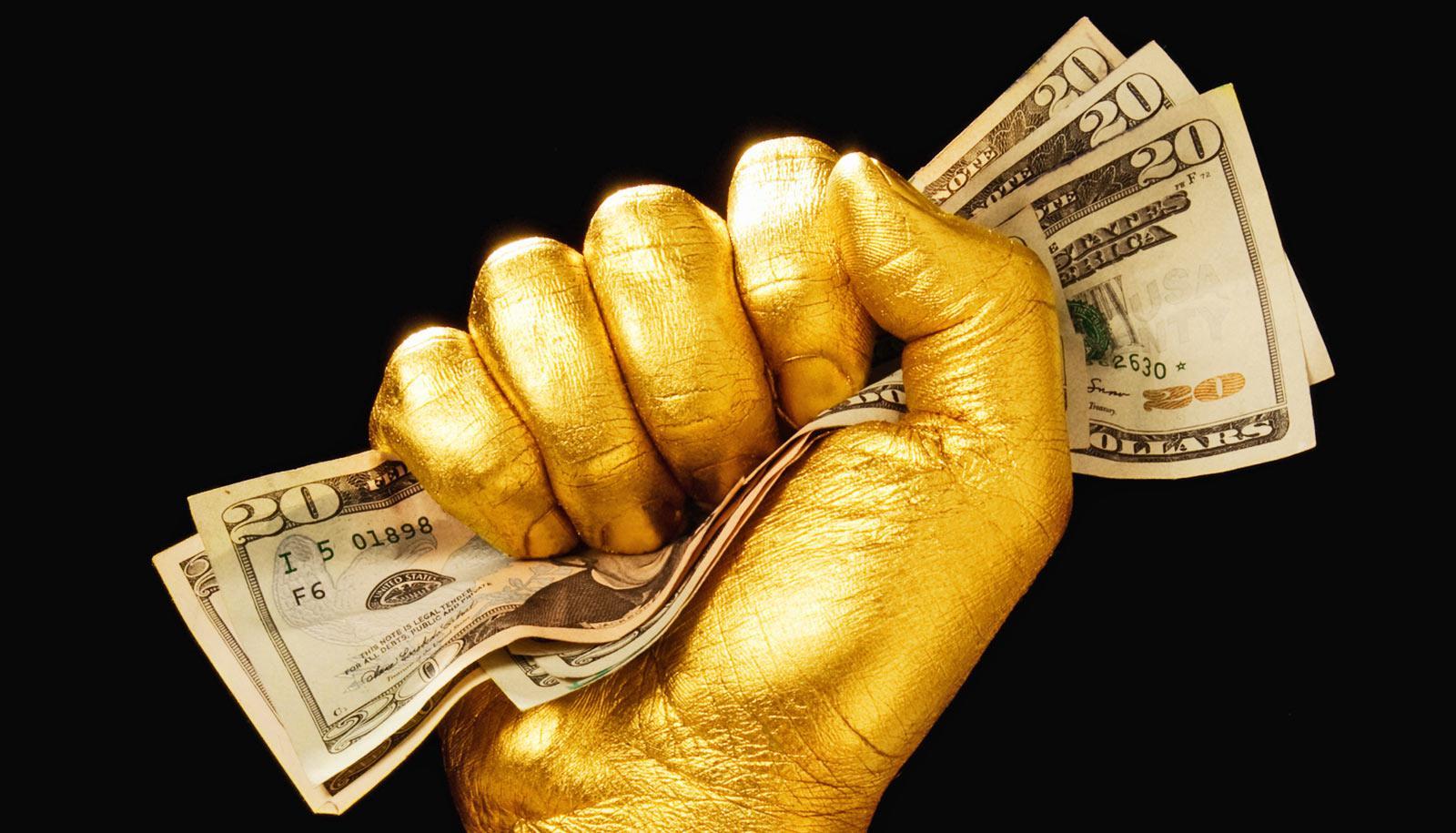 gold hand clutches $20 bills