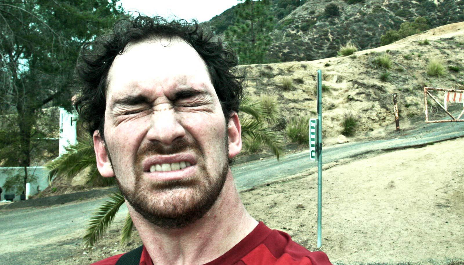 A man grimaces while sneezing outside on a walking trail