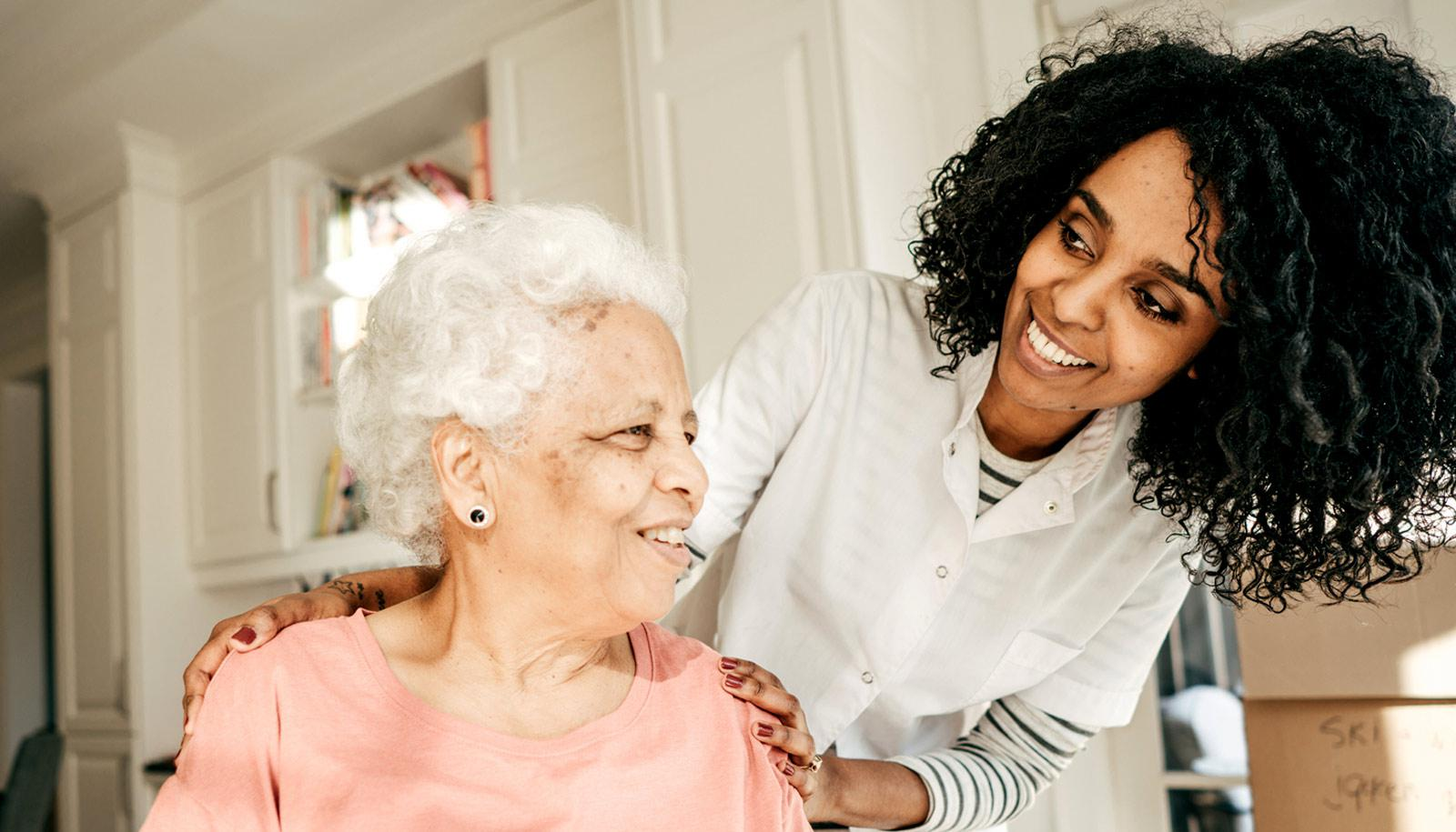 younger woman in white lab coat with elderly relative