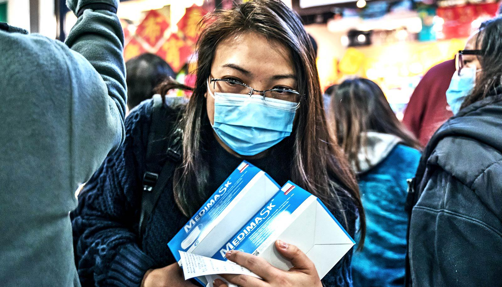 A woman wearing a blue medical masks carries two boxes of more medical masks as she moves through a crowd