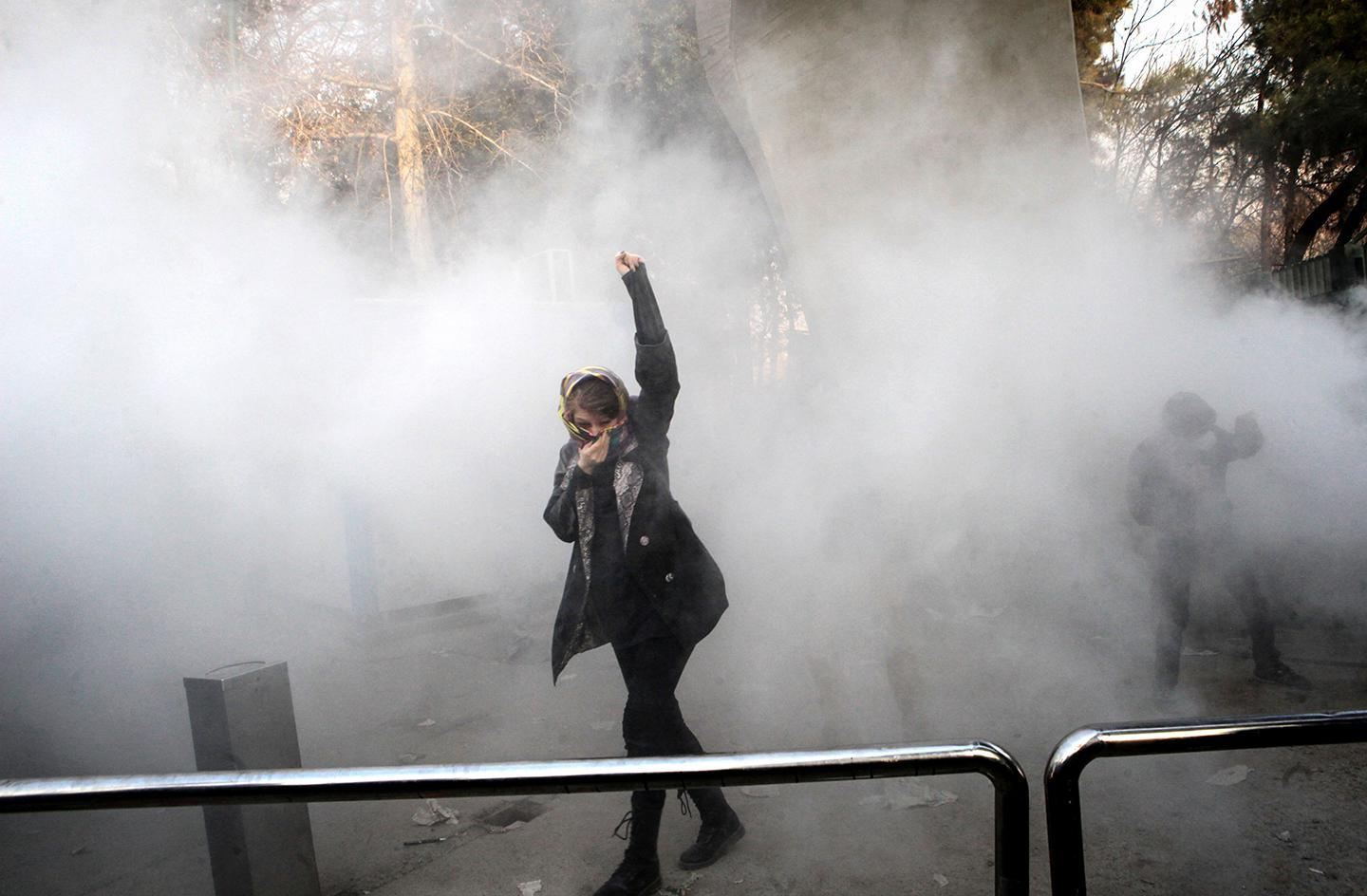 An Iranian woman raises her fist amid the smoke of tear gas at the University of Tehran during a protest driven by anger over economic problems, in the capital Tehran on December 30, 2017. Students protested in a third day of demonstrations sparked by anger over Iran's economic problems, videos on social media showed, but were outnumbered by counter-demonstrators.