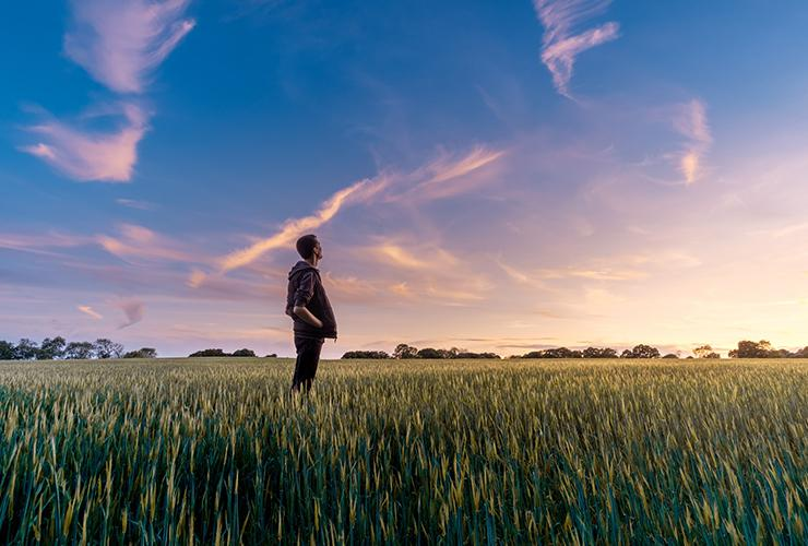 Prepare For Your Future With Mindfulness Practices and Positive Habits by Emily Murphy. Photograph of a man standing in a field looking up at the sky by Benjamin Davis