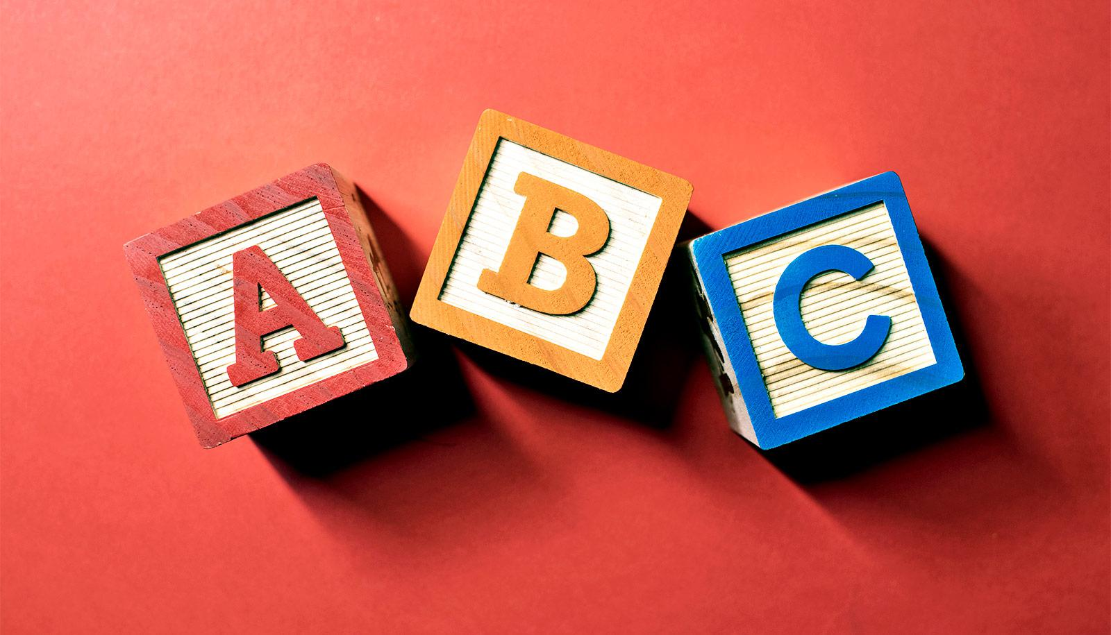 Toy ABC blocks sit on a red background