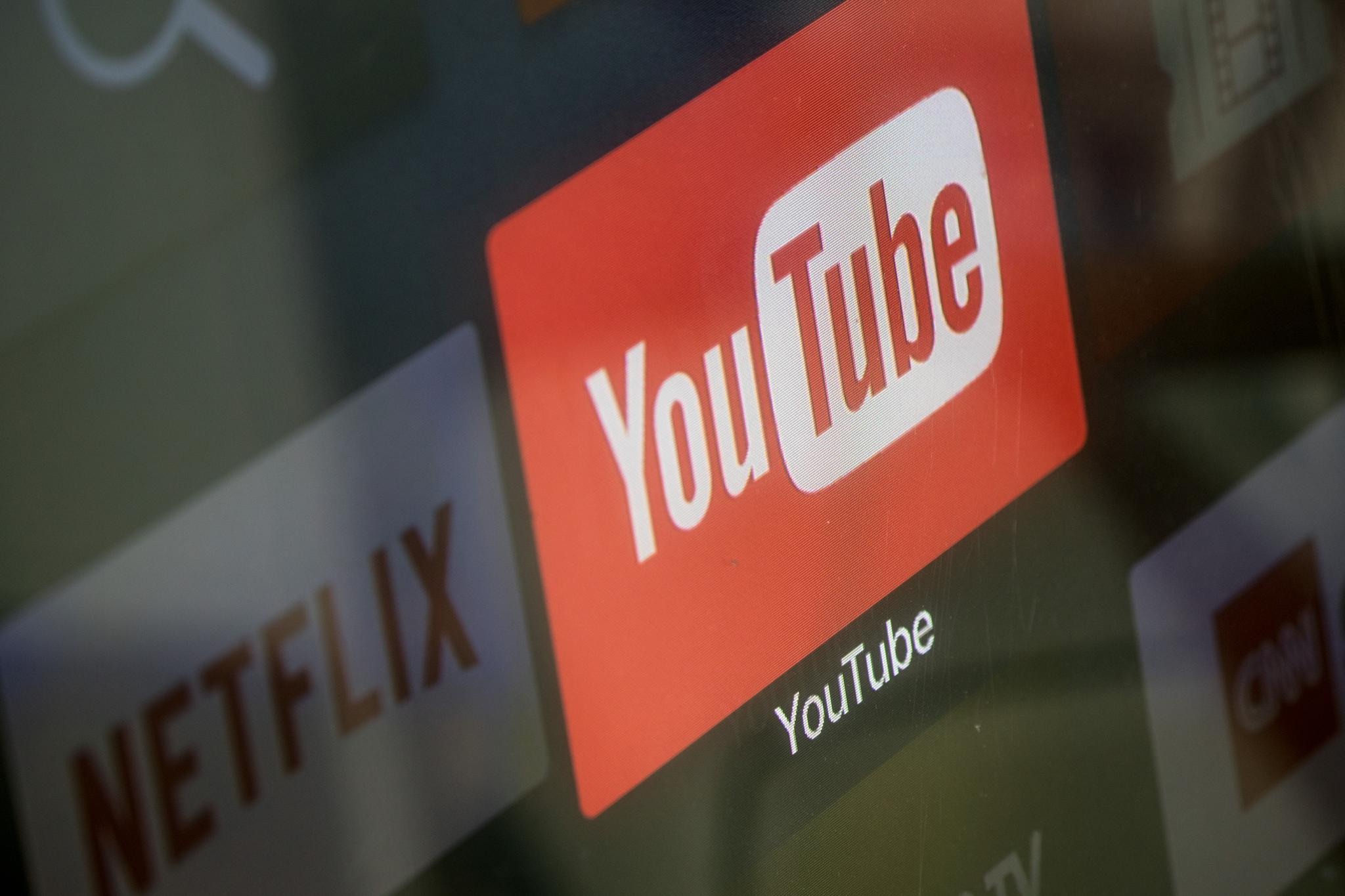 The YouTube and Netflix app logos are seen on a television screen on March 23, 2018 in Istanbul, Turkey. YouTube has drawn criticism for its role in spreading misinformation and conspiracy theories, but the platform is trying out new strategies to promote reliable sources.