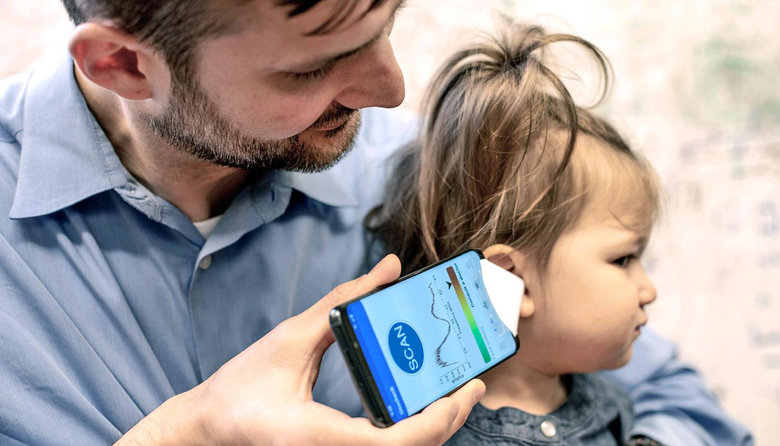 father holds ear infection app on phone to daughter's ear