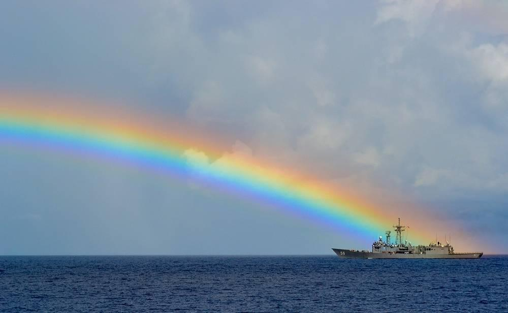rainbow over sea ship