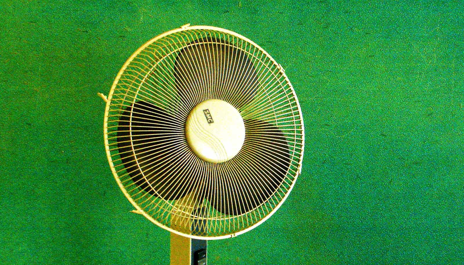 fan in front of green wall
