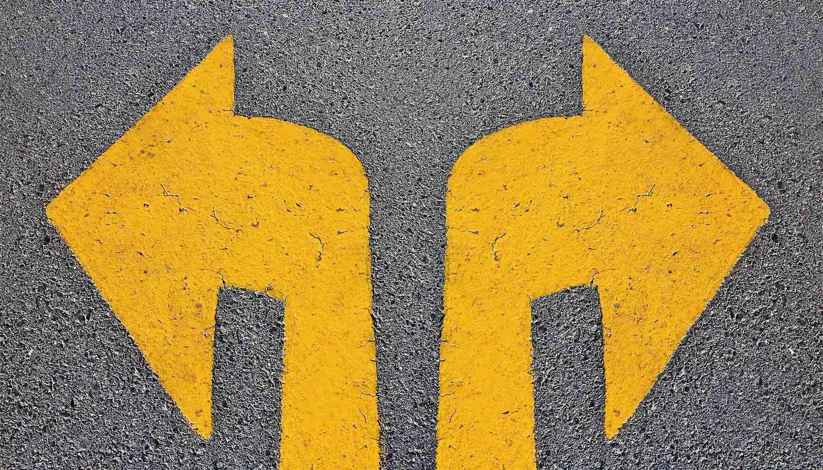 Two yellow arrows on asphalt point left and right