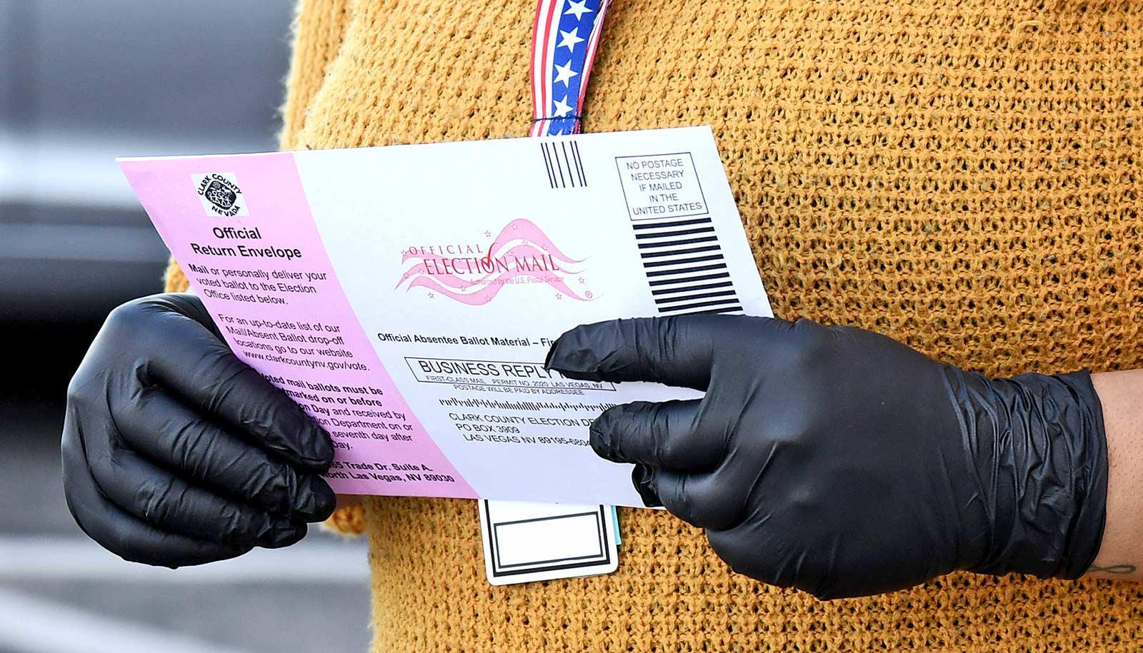 gloved hands hold ballot