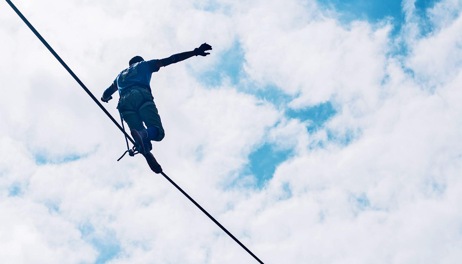 A person walks on a tightrope, balancing themselves as they go, against a cloudy sky