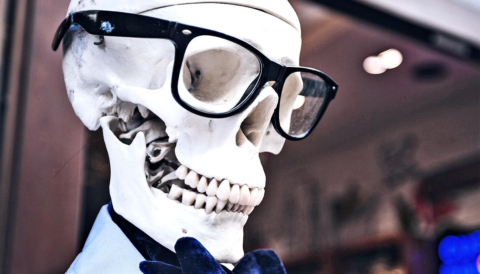 A skeleton wears glasses and a bow-tie on