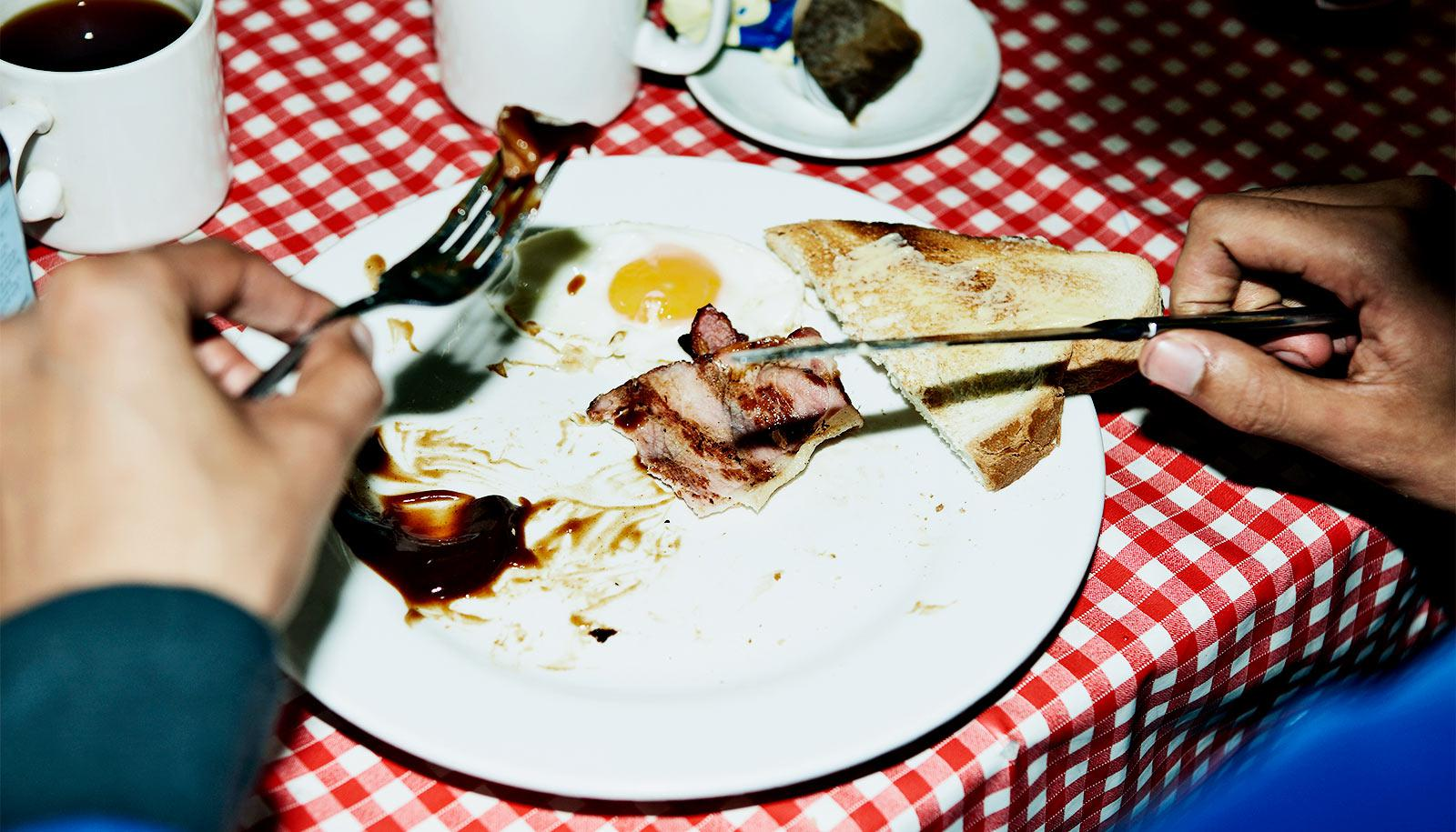 A man eats a plate of breakfast food that includes bacon, toast, and an egg. The plate is sitting on a red and white checkerboard table cloth while the man holds utensils in each hand