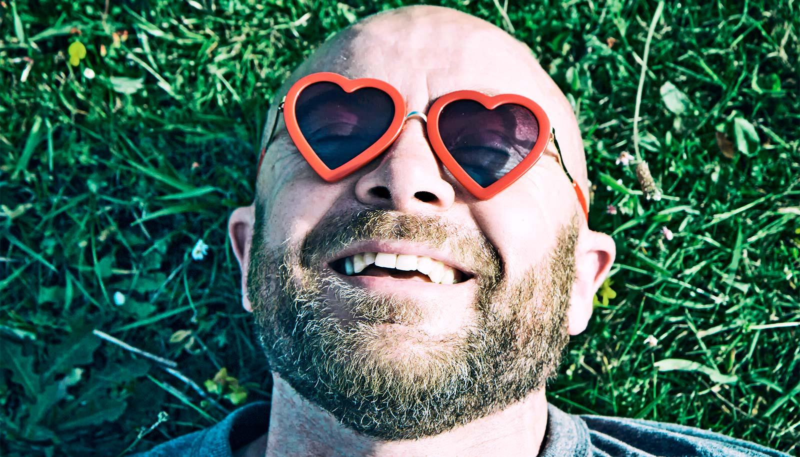 A bald man wearing heart-shaped glasses smiles with contentment as he lies on grass
