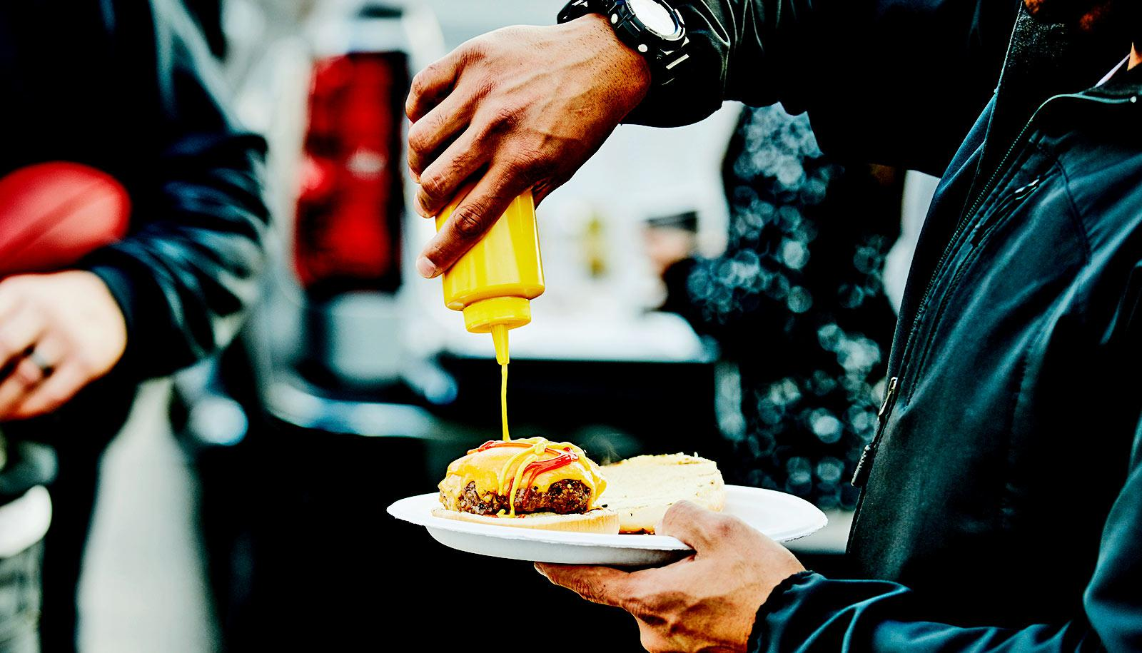 A man squeezes mustard onto a burger while tailgating
