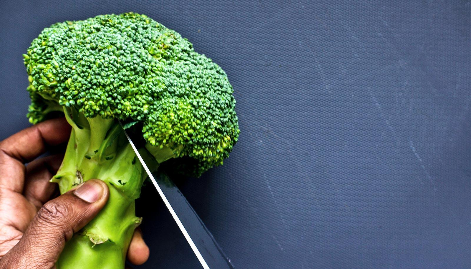 A person cuts a broccoli floret against a dark blue background (indole)