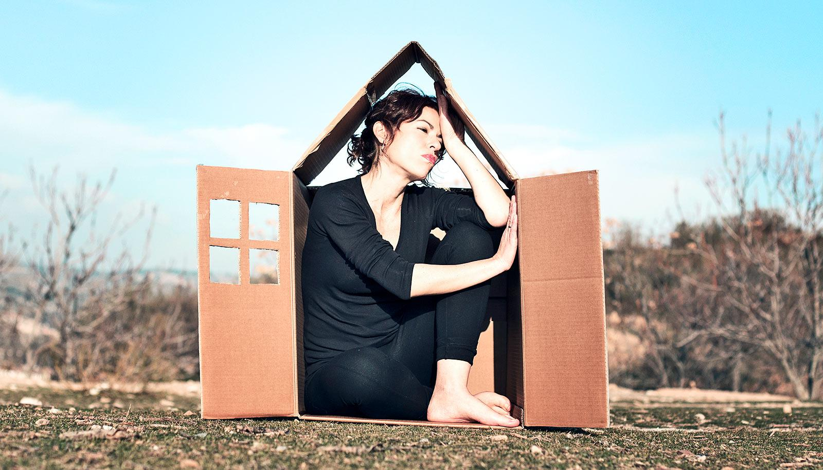 A woman sits looking anxious in a box cut to look like a tiny house