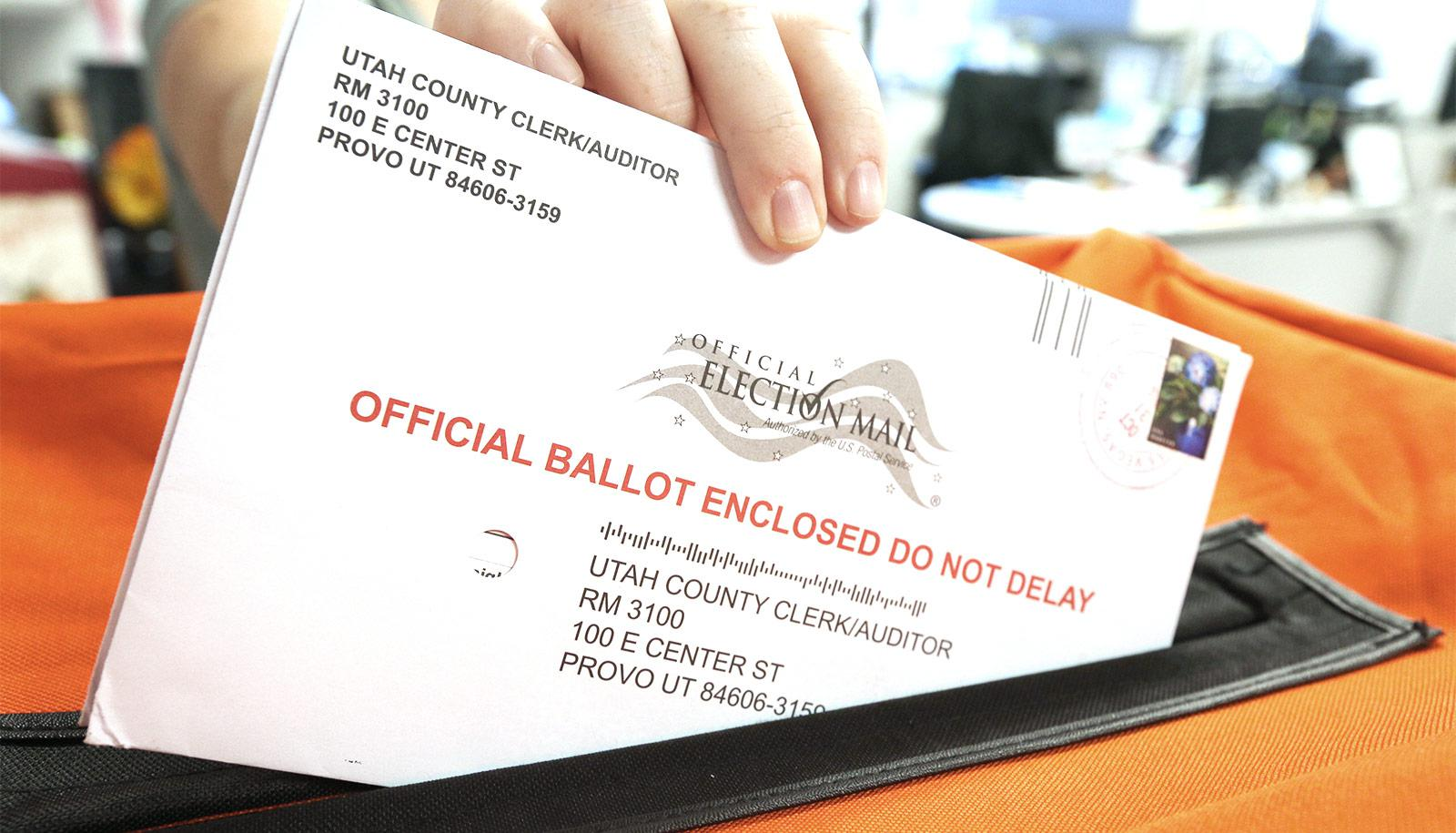 A person slides a mail-in ballot into an orange container