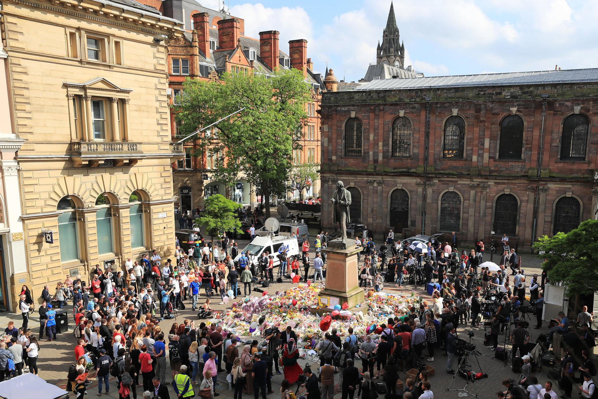 People look at flowers in St. Ann's Square, close to the Manchester Arena where a suicide bomber killed 22 people leaving a pop concert at the venue on Monday night.