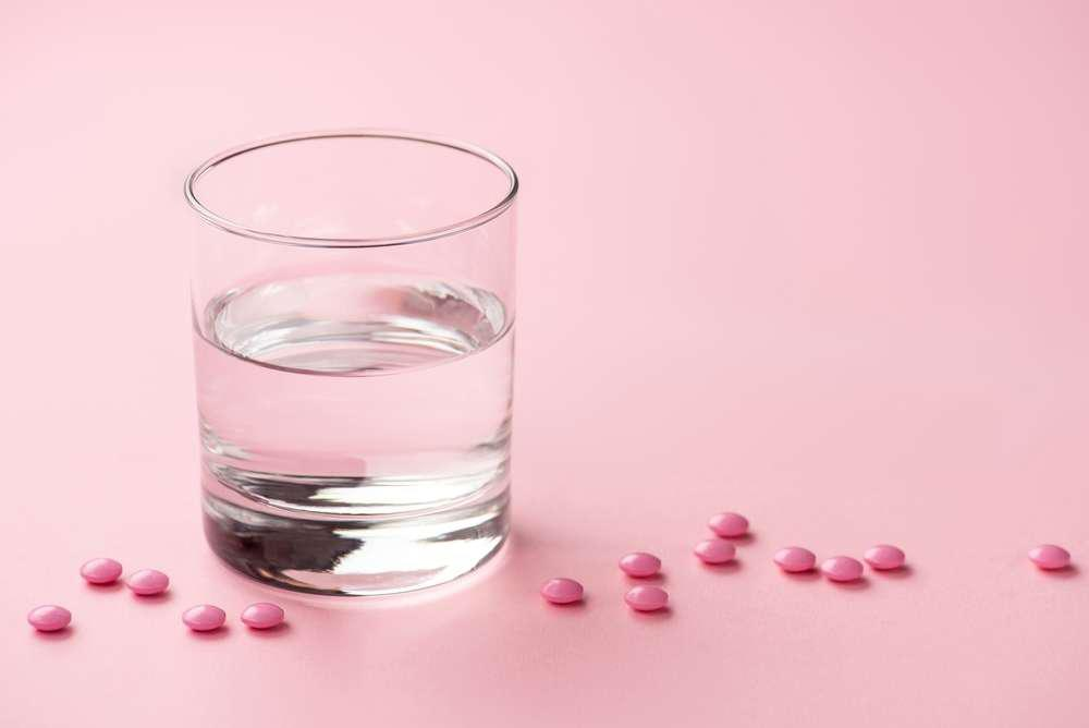 a glass of water and pink pills on a pink background