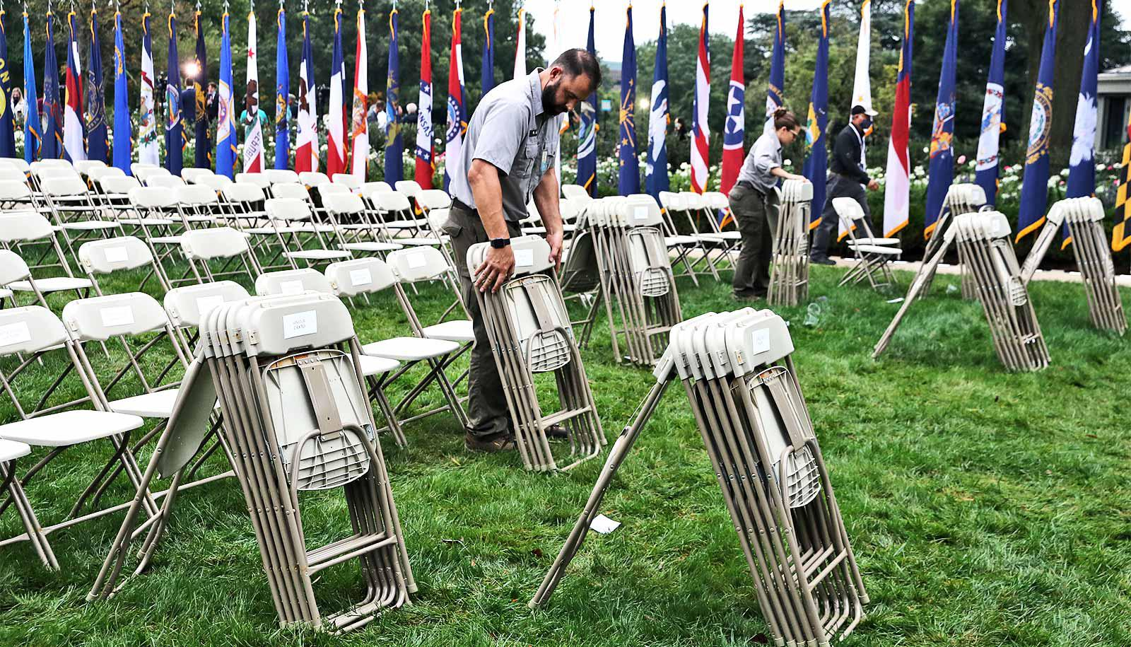 A man sets up folding chairs on the White House's Rose Garden lawn