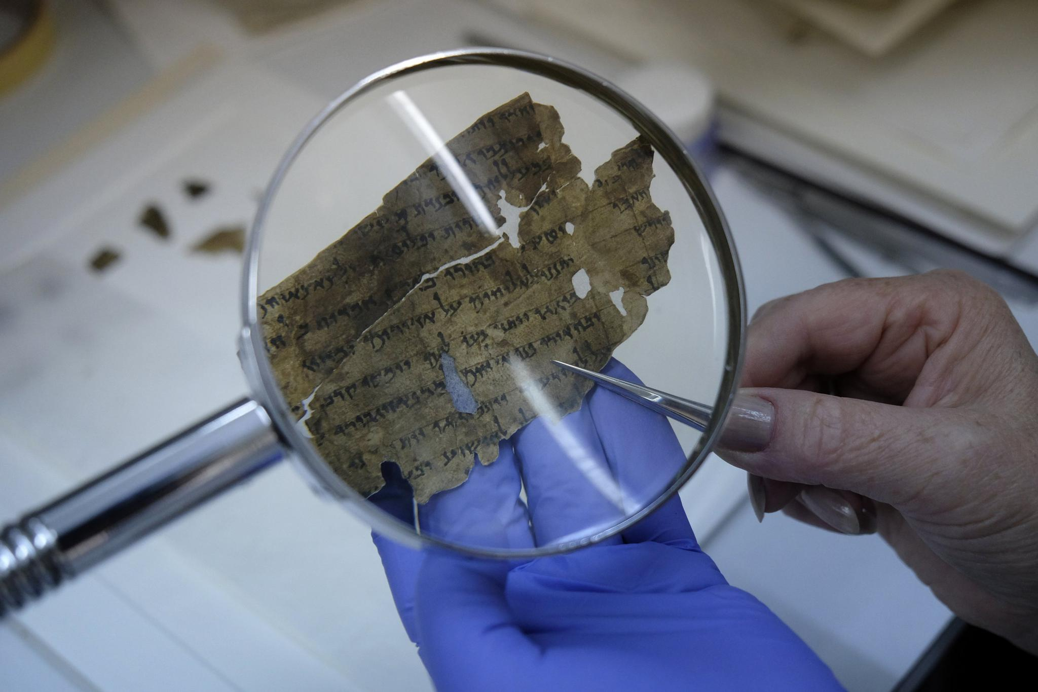 An employee of the Israel Antiquities Authority sews fragments of the Dead Sea scrolls in a preservation laboratory at the Israel Museum in Jerusalem on July 20, 2015.