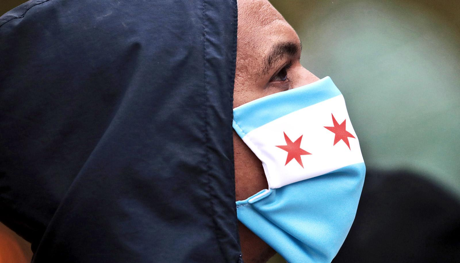 A man wears a mask with blue stripes and red stars in a white bar to prevent coronavirus transmission