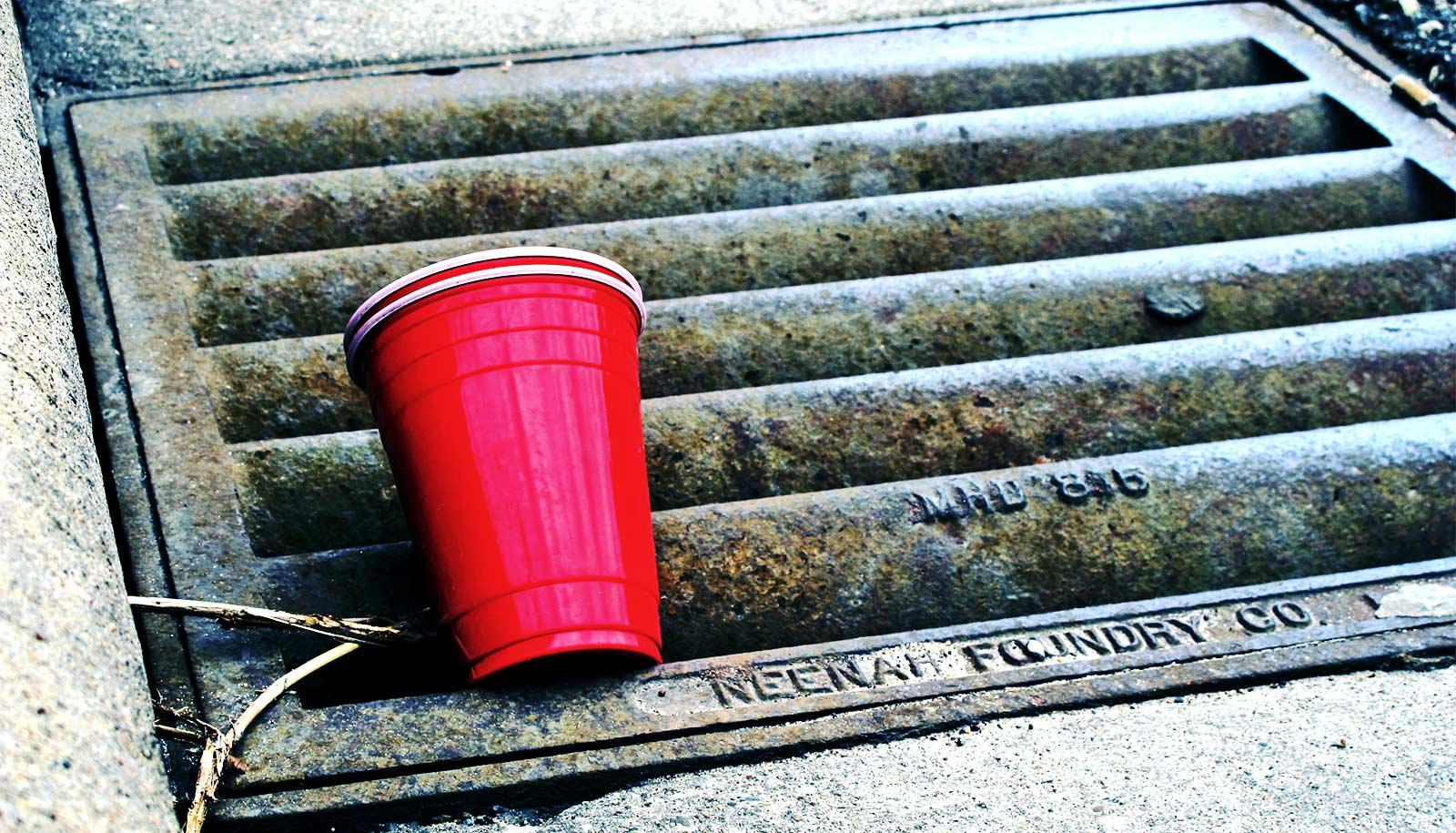 A red solo cup sits on a sewer drain on the street