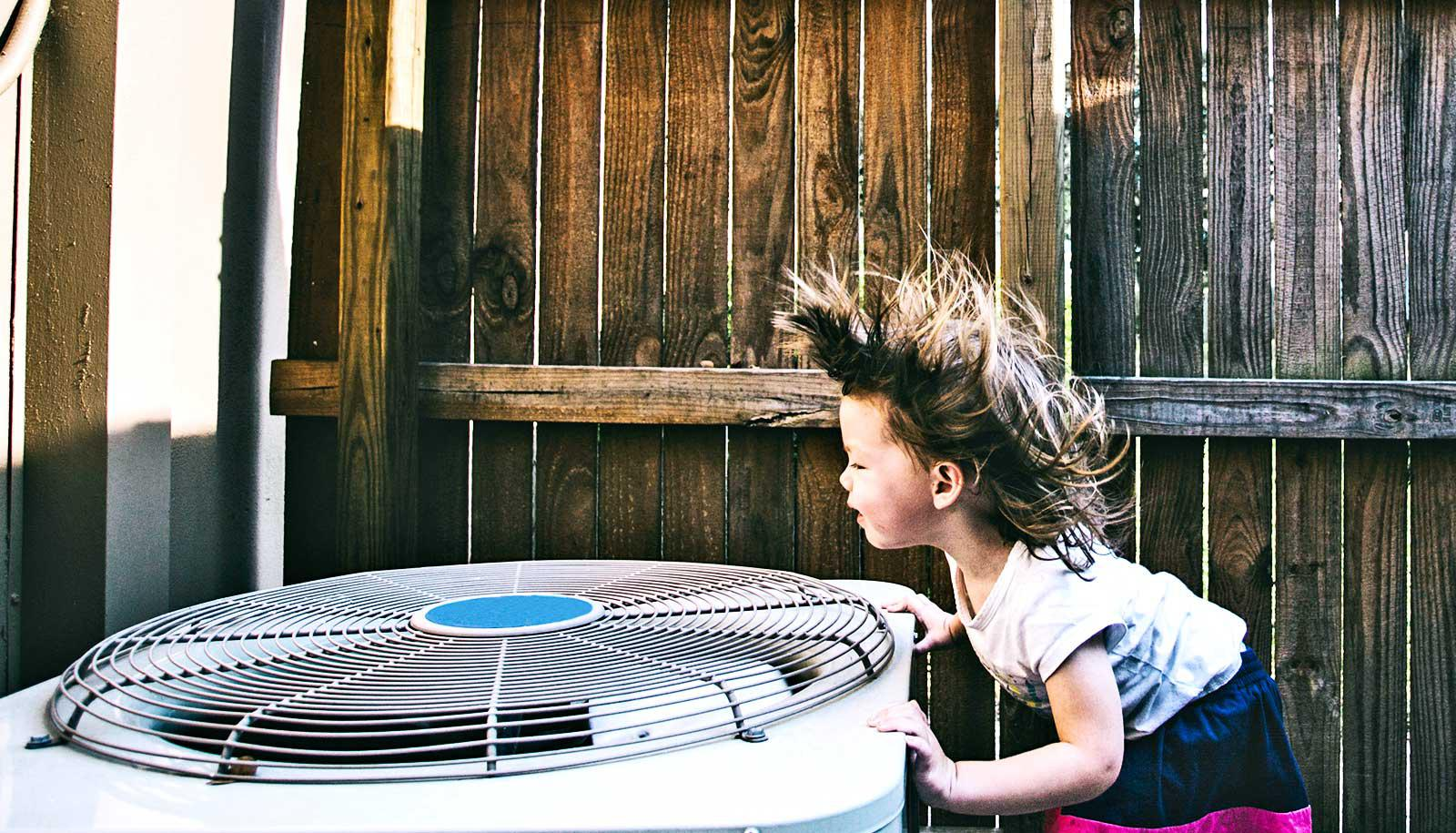 A young girl leans over an air conditioner unit as the air blows her hair up. Behind her and the AC unit, there's wooden fence