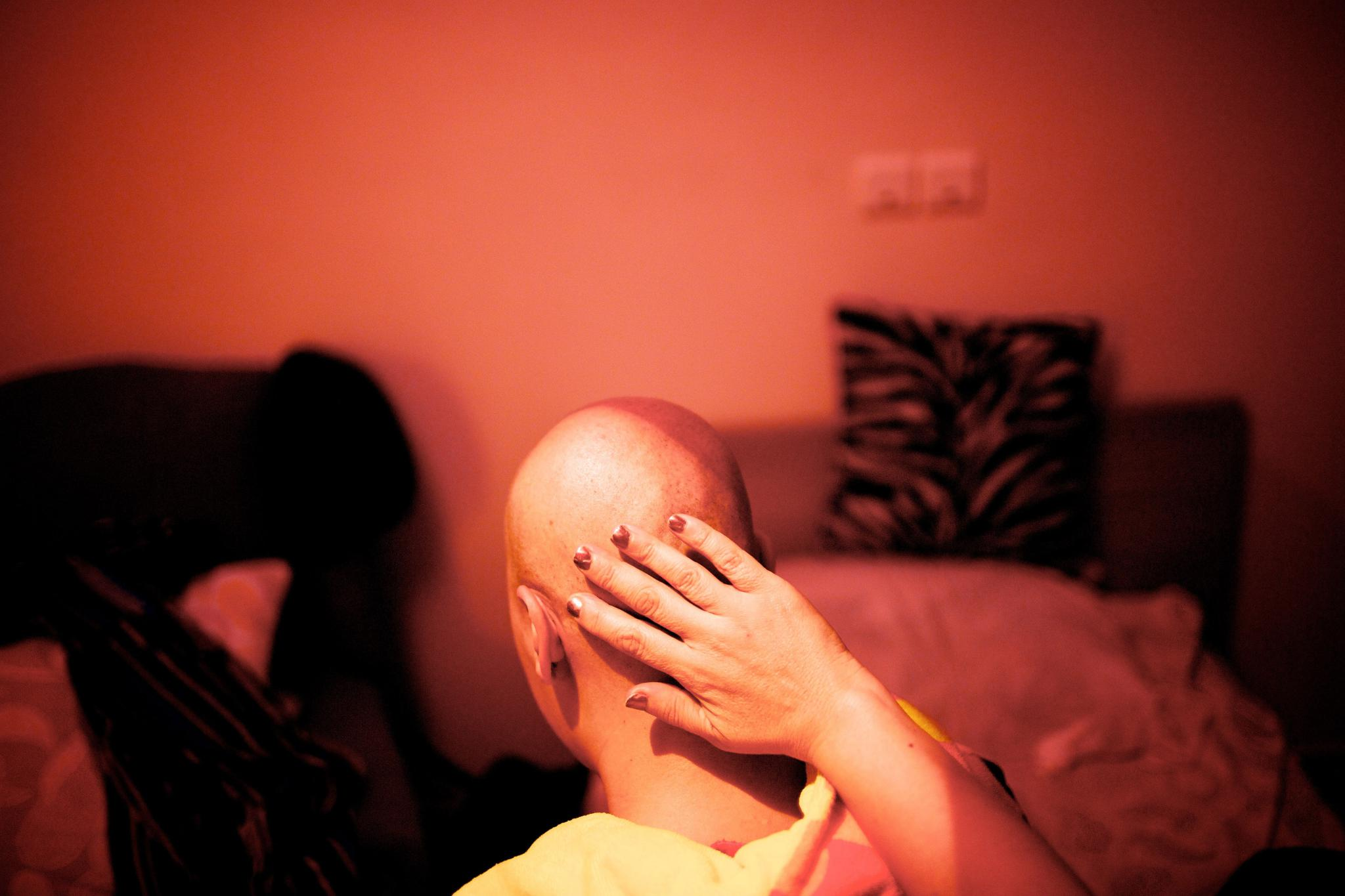 An Iranian breast cancer patient's mother massages her head after lumpectomy surgery.