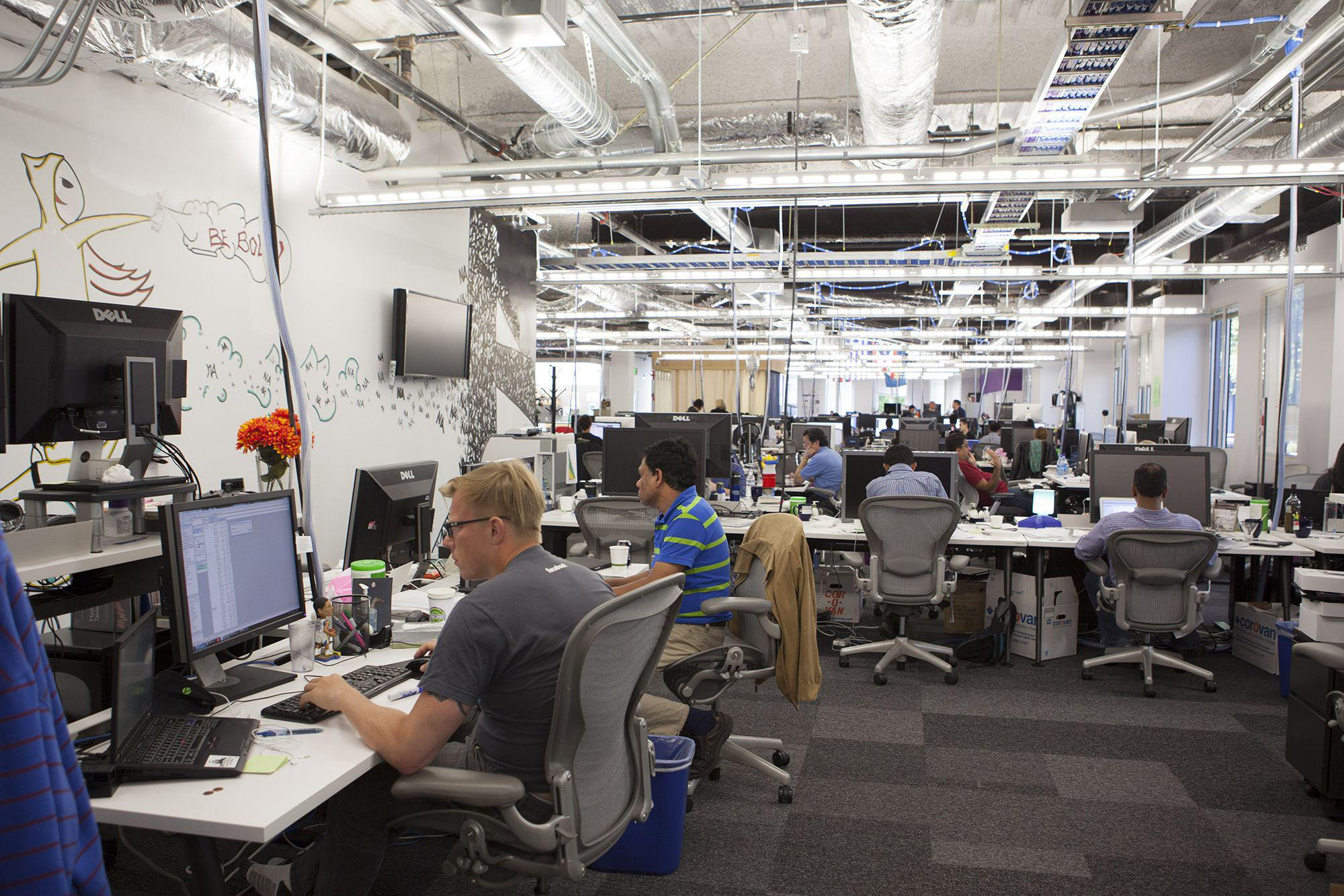 Scenes of daily work and life at Facebook , Inc. USA Headquarters in Menlo Park, California. View of employees at work in a typical unfinished looking workspace.