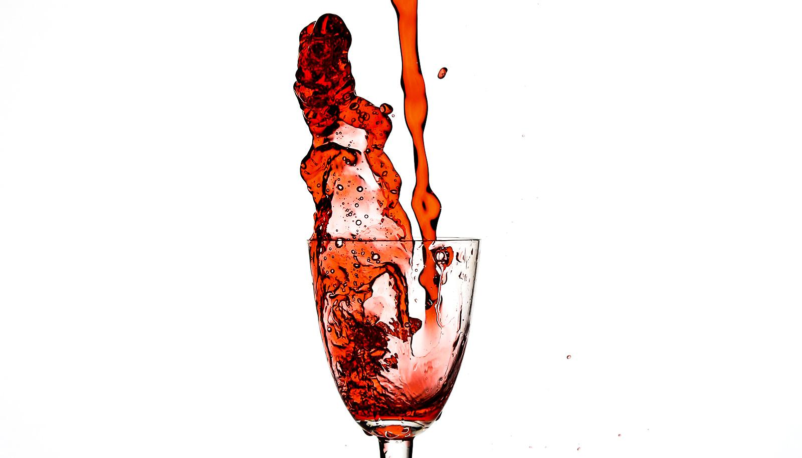 Red wine pours into a glass and then splashes out