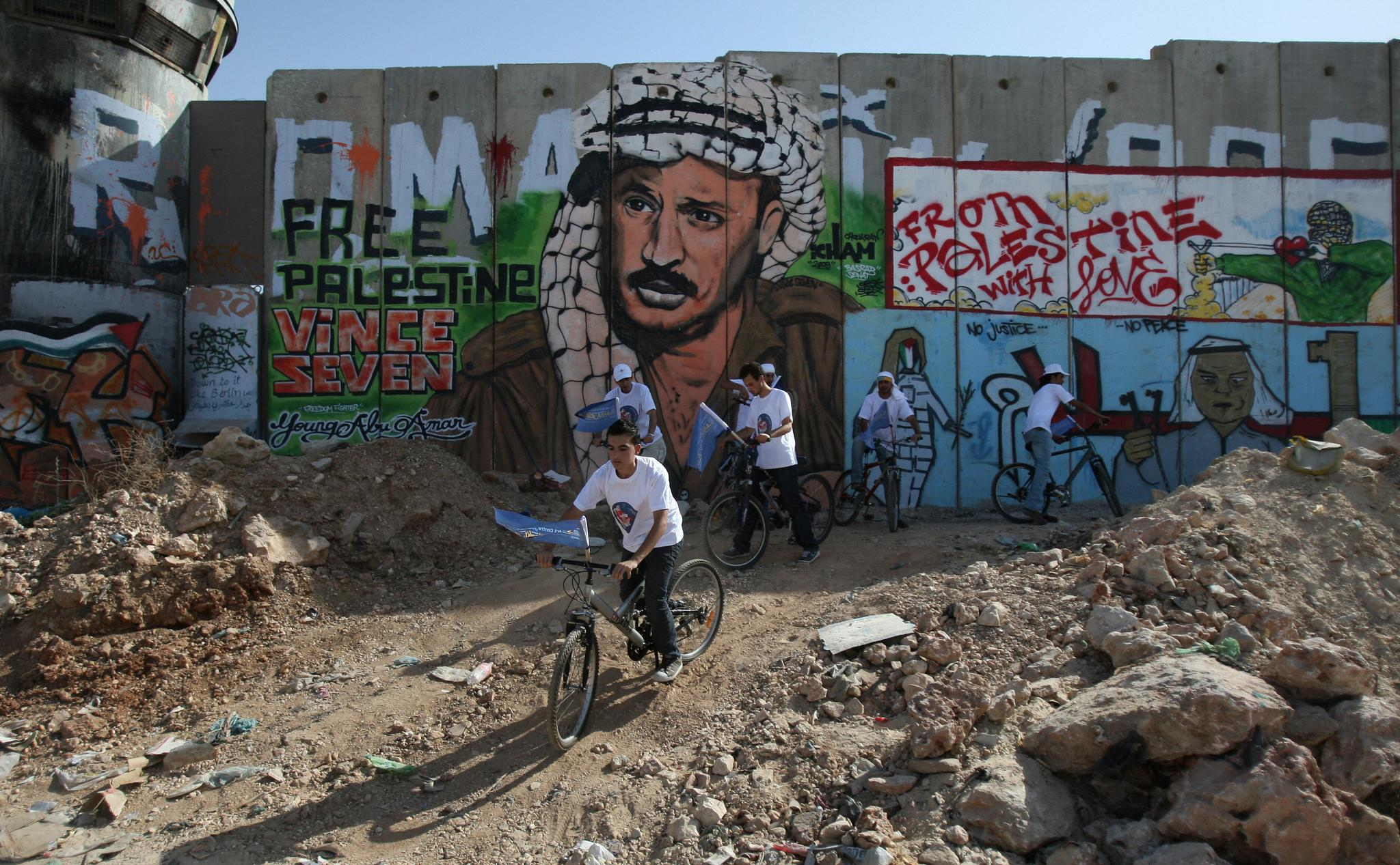 A group of Palestinian youths cycle past a section of Israel's separation barrier to promote a cultural festival in the West Bank city of Ramallah and as a protest against the wall on June 30, 2009 in the Qalandia checkpoint between northern Jerusalem and Ramallah.