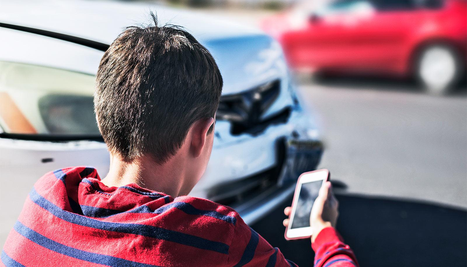 A teen in a red shirt looks at their phone while sitting on the curb, ready to call, at the scene of a car accident