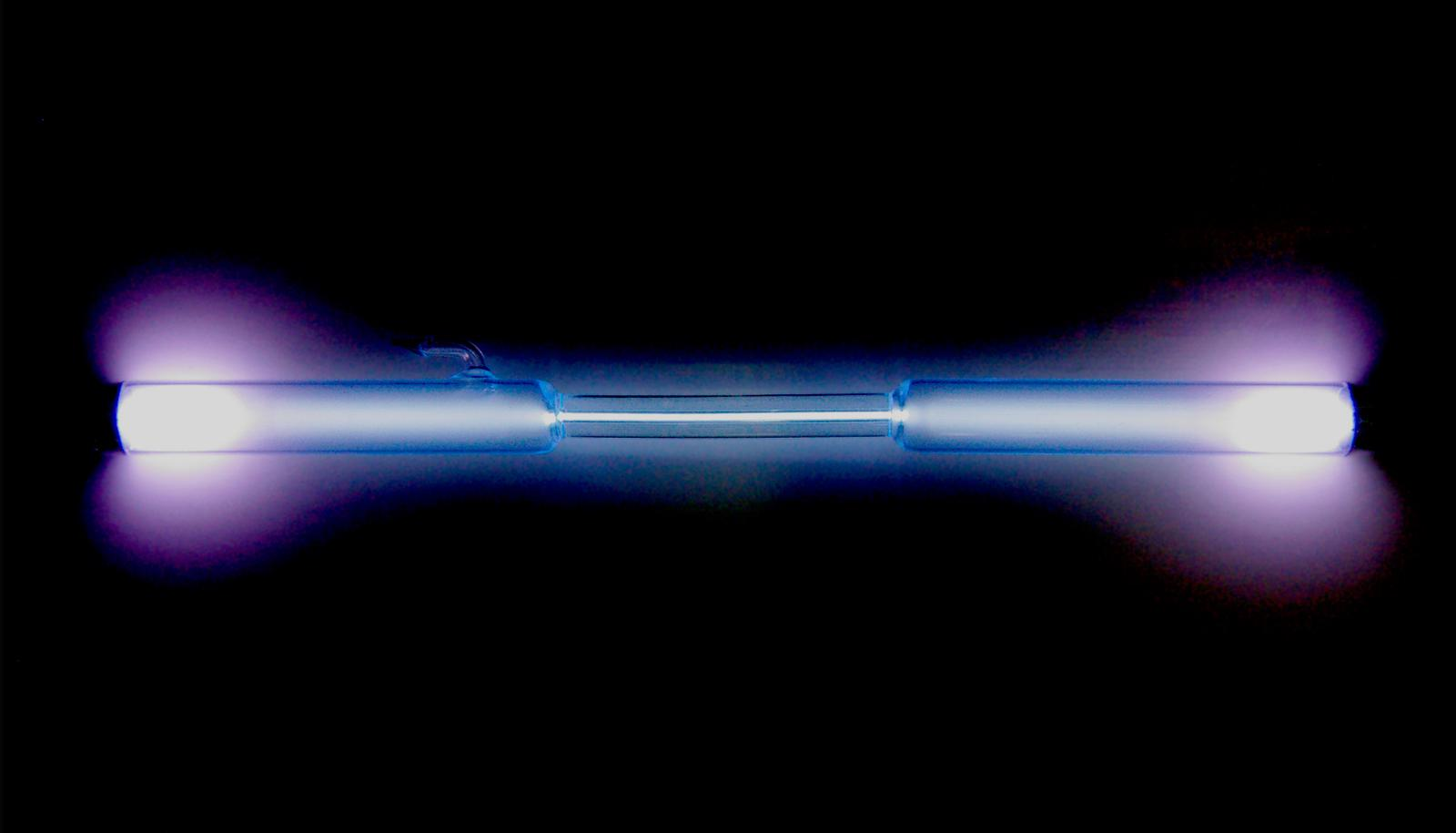 tube of xenon glows blue and purple on black