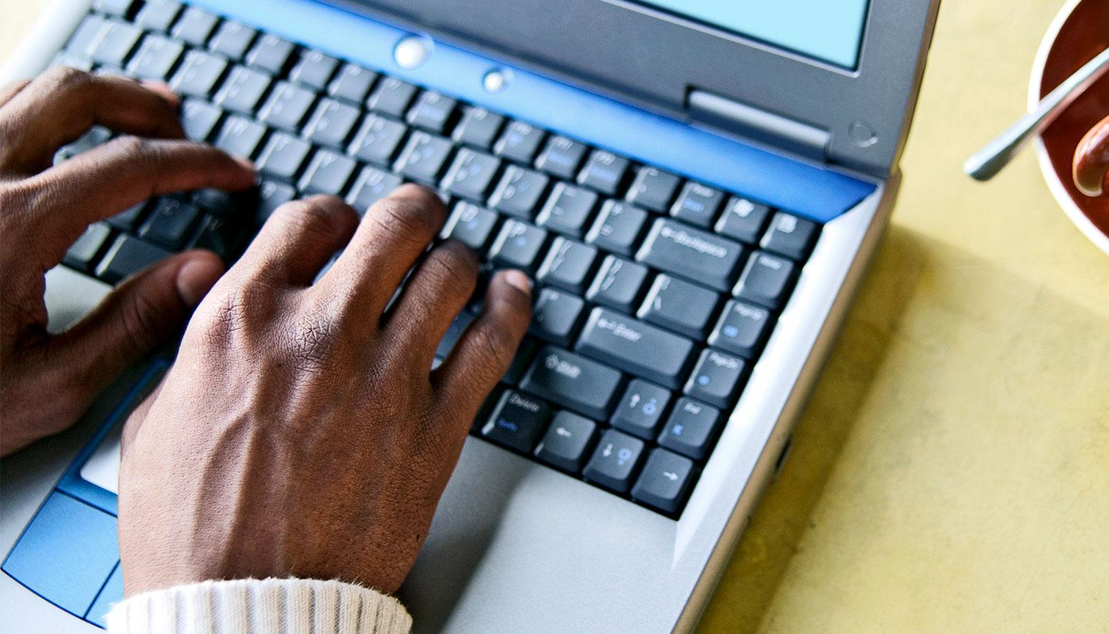 Hands sit on an old laptop computer keyboard on a yellow table
